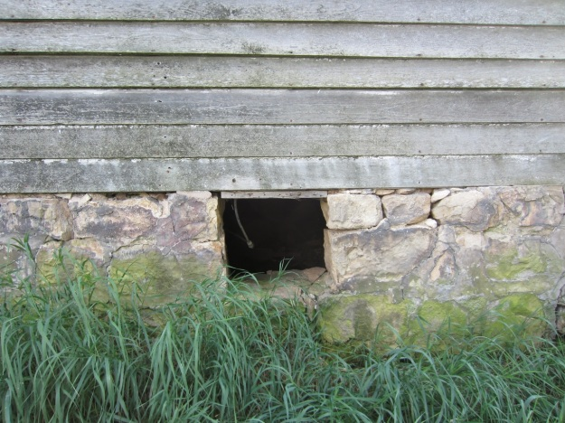 Crawl space vent, located on framed addition.  Original log core contains a full depth cellar and later framed addition just a crawl space.