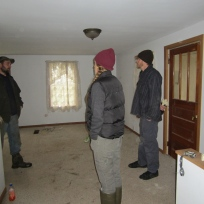 Inside stue room. Primary entrance behind Hans, which leads into enclosed porch and attached summer kitchen.