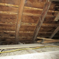 Roof rafters made of peeled trees hewn flat on one side to accept roof boards.