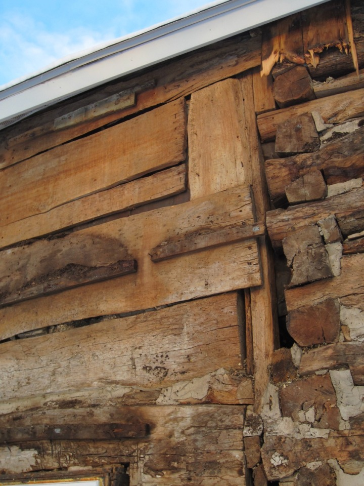 """Notice framing of 2nd floor addition.  The vertical piece is a log and the horizontal sheathing boards vary from 1"""" thick to 2"""" thick."""